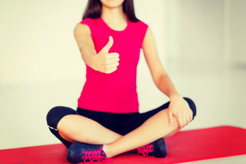 girl sitting in lotus position with thumbs up