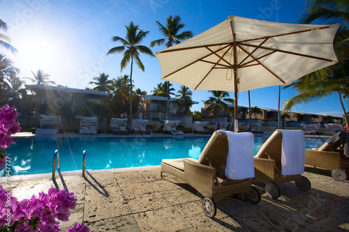 Foto Spatwand Eilanden art Deckchairs in tropical resort hotel pool