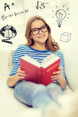 smiling teenage girl reading book on couch