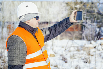 Engineer filmed with tablet PC destroyed building in winter