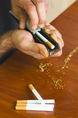 Man rolling cigarettes using fresh tobacco