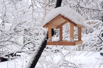 wooden bird table topped with fresh snow
