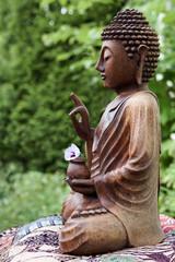 Wooden buddha statue in garden with flower
