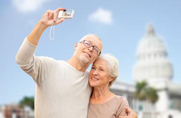 senior couple with camera over white house
