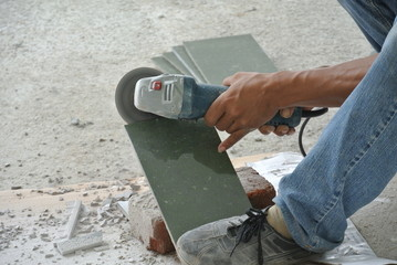 Construction workers using grinder to cut tiles
