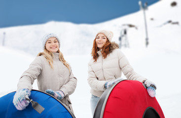 happy girl friends with snow tubes outdoors