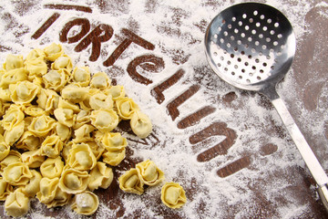Fresh tortellini and utensil with flour on table