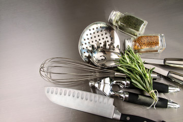 Kitchen utensils and herbs on stainless steel