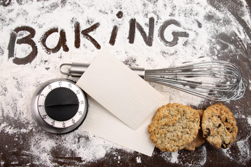 Word baking written in flour and cooking utensils on wooden tabl