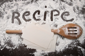 Word recipe written in white flour and spatula on wood