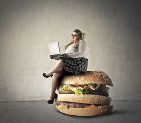 Chubby woman sitting on a giant hamburger
