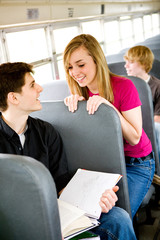 School Bus: Girl Talks to Guy Doing Schoolwork