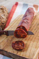 Spanish sausage with bread over a wooden table