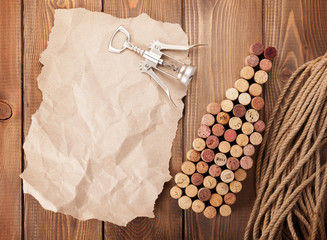 Wine bottle shaped corks, corkscrew and piece of paper for copy