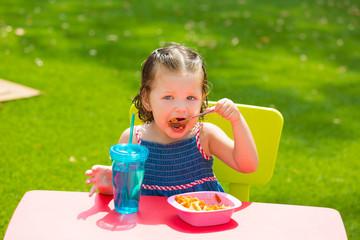 Toddler kid girl eating macaroni tomato pasta