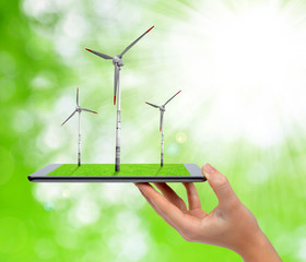 Hand holding digital tablet with a wind turbines.
