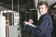 Leinwanddruck Bild - maintenance engineer checking technical data of heating system e
