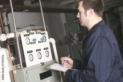 maintenance engineer checking technical data of heating system e - 77954773