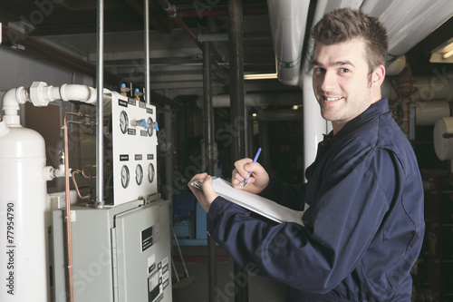 Leinwanddruck Bild maintenance engineer checking technical data of heating system e