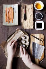 overhead shot of hands slicing a roll of hosomaki sushi