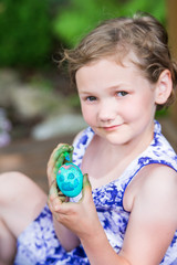Happy Little Girl Poses with Painted Easter Egg
