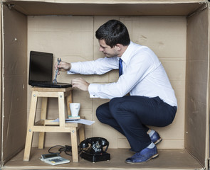 businessman trying to mend itself own computer