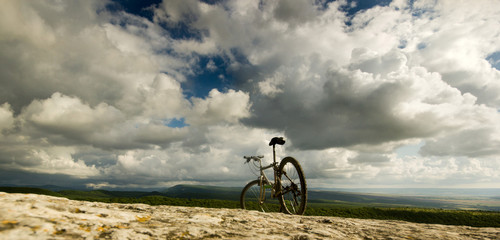 bicycle on a cliff with covered by forest hills