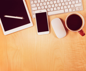 Office table with digital tablet, smartphone and cup of coffee.
