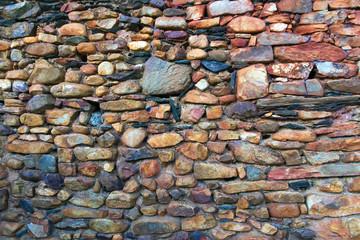 Muro de piedra, cantos y lajas con oxidos rojizos