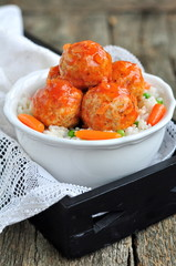 Pork meatballs with rice, carrots, peas and red sauce