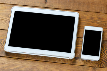 Tablet and smartphone on an old wood