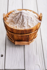 flour in wooden bucket with handle on old white painted