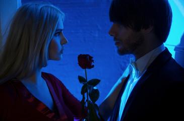 Red rose between people in love