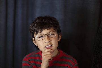 Quizzical young boy in glasses