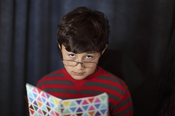 Young boy in glasses looks over book