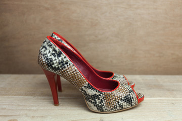 Snake leather woman shoes with red details close up