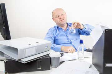 Drunk businessman drinks alcohol at the office