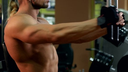 Side view of muscular man training his hands in the gym, slow