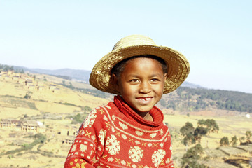 Smiling african boy with hat on head, poverty in Madagascar