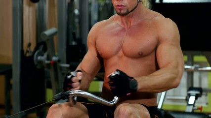 Muscular man training and using pull the lower unit in gym