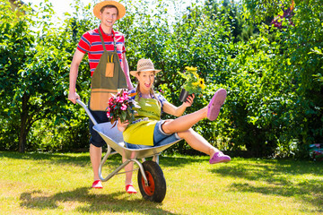Paar im Garten mit Kanne und Schubkarre