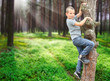 Little boy climbing on tree and enjoying summer holidays.