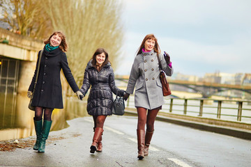 Three cheerful girls walking together in Paris