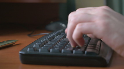 4k - Close-up of a young man hands typing on a laptop keyboard