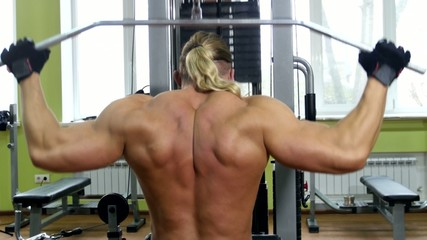 Back view of bodybuilder doing exercises on the trainer