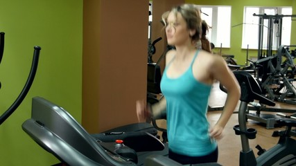 Athletic girl doing an exercise on running track in the gym