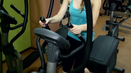 Athletic girl doing an exercise on fitness track in the gym