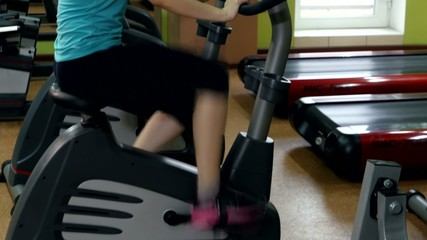 Attractive girl in fitness hall is cycling, cam moves upwards