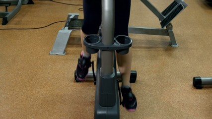 Sporty girl is cycling in fitness gym, cam moves upwards, slow