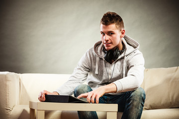 Young man with tablet headphones sitting on couch
